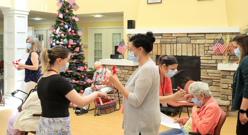 Staff members at Ingersoll Place Assisted Living distribute red poppies to residents during a Memorial Day program Thursday.