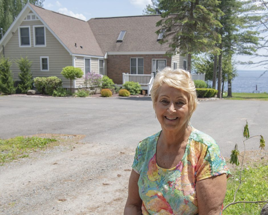Joanna Olson, a broker with Howard Hanna Real Estate, on Wednesday stands in front of a home on the Great Sacandaga Lakeon Route 30 in Mayfieldthat she sold.