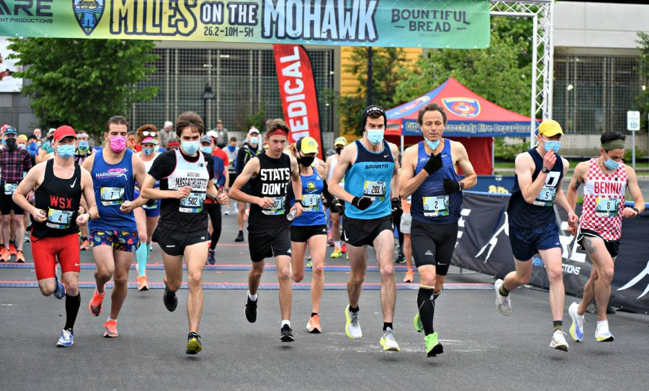 Runners leave the starting lineto beginthe marathon run Sunday morning atMohawk Harbor during the Miles on the Mohawk races.