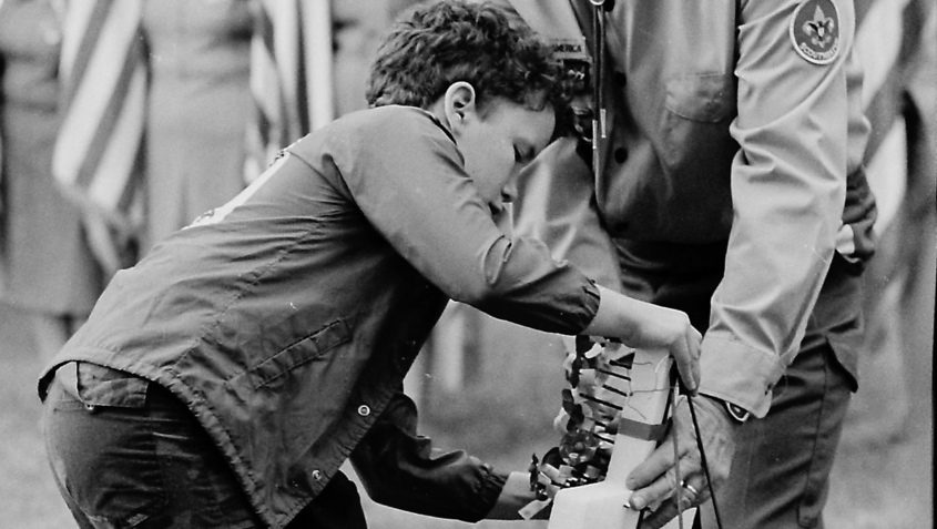 A boy pins a poppy on a memorial honoring deceased war veterans on the grounds of American Legion Post 1005 on Chrisler Avenue. The ceremony was part of the annual Memorial Day observance in Mont Pleasant in 1984.
