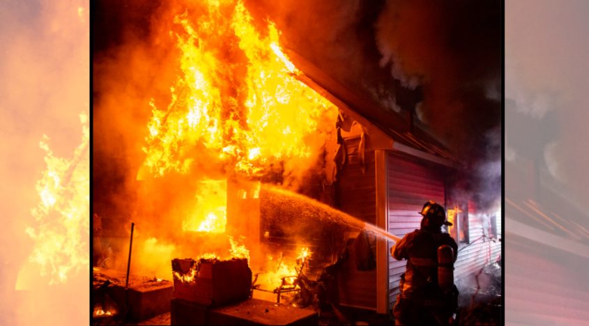 Schenectady firefighter Michael Farber trains water on the back of the house