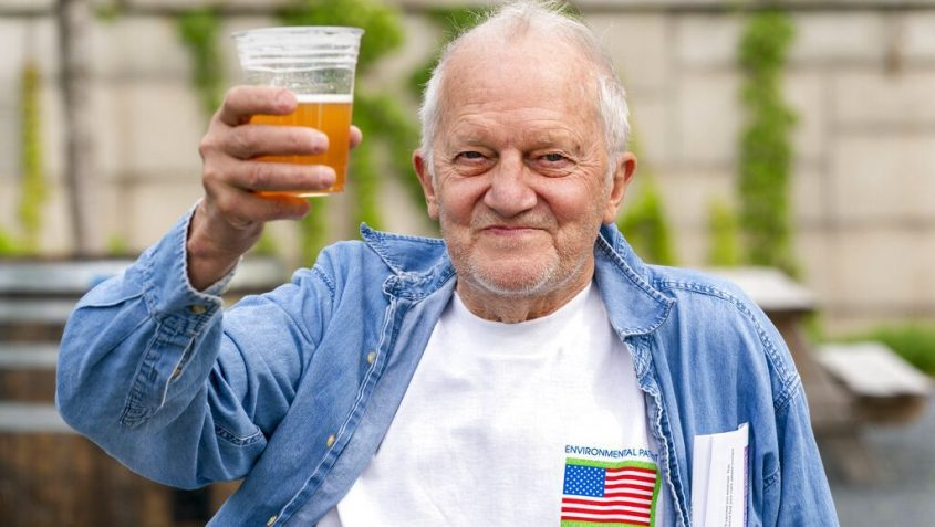 In this May 6 photo, George Ripley, 72, of Washington, holds up his free beer after receiving the J & J COVID-19 vaccine shot, at The REACH at the Kennedy Center in Washington.