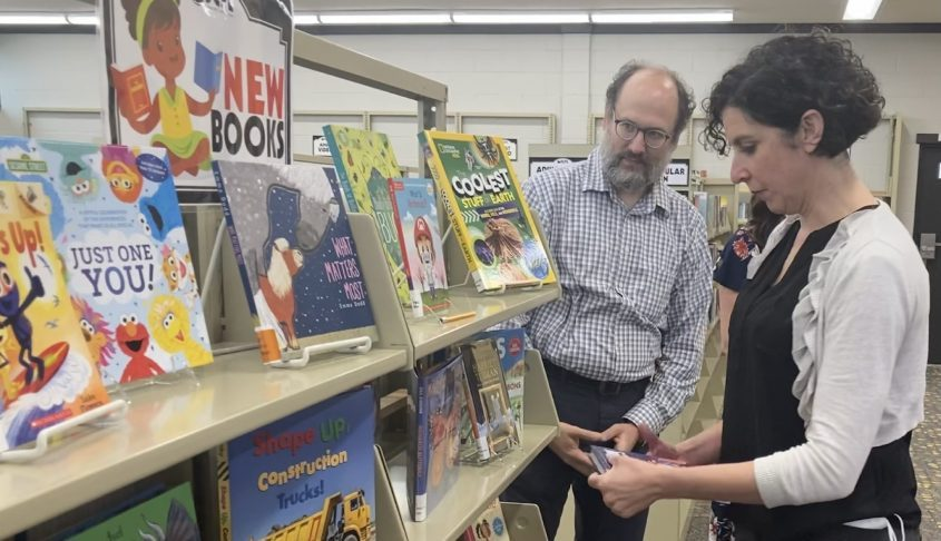 Kaela Wallman, youth services coordinator at the Woodlawn branch of the Schenectady County Public Library System, seeks out a children's book while Assistant Library Director Devon Hedges looks on Friday. Renovations at the branch were recently completed and the library reopens Monday.