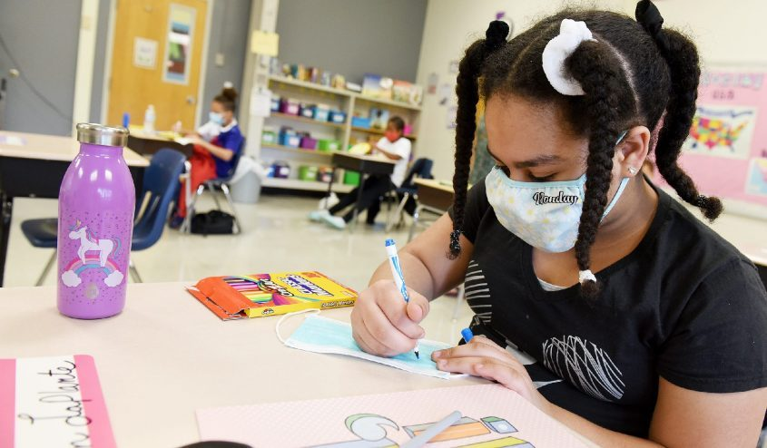 """Fifth-grade student Jaelyn LaPlante, 10, decorates her fresh """"back-up"""" mask for her desk at at Zoller Elementary School on the first day of hybrid learning for students and teachers in Schenectady on Sept. 14."""