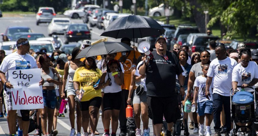 Tom Mueller, center, an activist with the Capital Region Cares Coalition, leads a group of approximately 100 people up Clinton Street in Albany as part of the Unite: Stop the Violence march on Saturday afternoon.