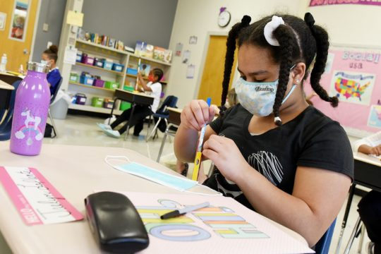 "Fifth grade student Jaelyn LaPlante, 10, decorates her fresh ""back-up"" mask for her desks at Yates Elementaryin September 2020."