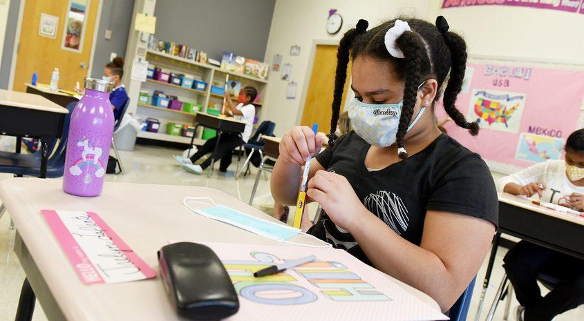 "Fifth grade student Jaelyn LaPlante, 10, decorates her fresh ""back-up"" mask for her desks at Yates Elementaryin September."