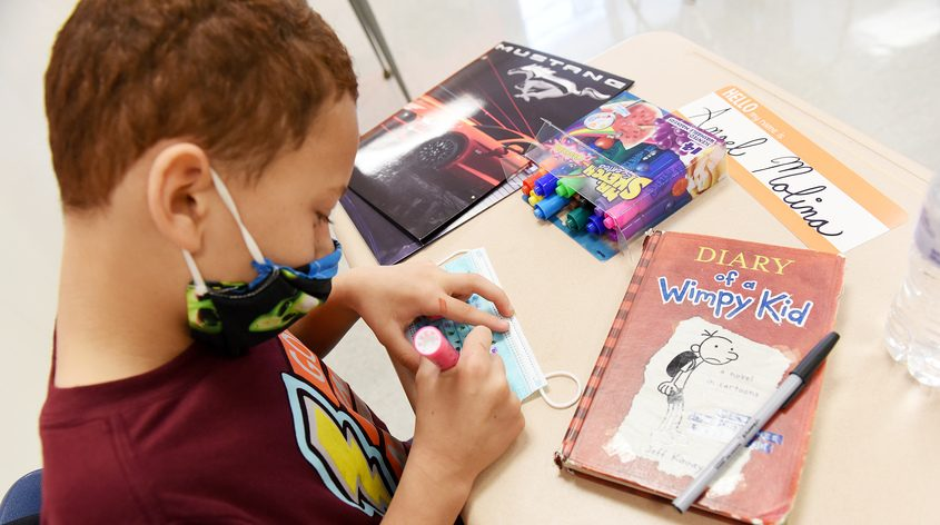 """Fifth grade student Angel Molina, 10, decorates his fresh """"back-up"""" mask for his desks at Yates Elementary in September"""