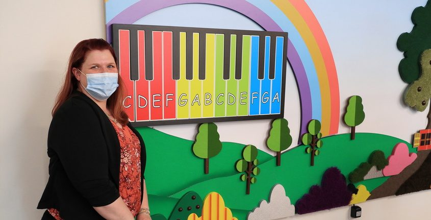 Practice administrator Christina Moran, stands beside a tactile sensory wall (with working piano keyboard) at Ellis Medicine's new and expanded child, adolescent and family mental health center in Schenectady Tuesday