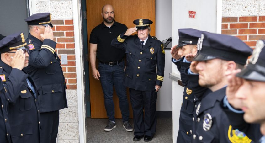 Outgoing Niskayuna interim Police Chief Fran Wall, center, salutes fellowofficers as she walks out of Niskayuna Town Hall with her son Don Wall on Friday.