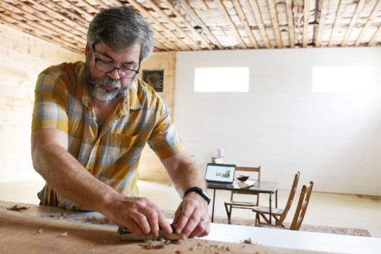 Jason Nemec works on revealing walnut grains with a wood block plane for a custom standing desk in the former Charlton Volunteer Firehouse on Tuesday.Nemec is in the process of converting the space into his design workshop and studio, which will include a gallery in the front.