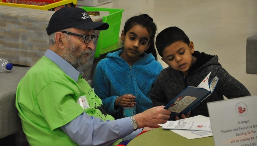 Al Magid, founder of Reading is Fun, reading a book with elementary children as part of the volunteer group's efforts to improve reading skills for Schenectady's children. The photo was taken during a 2019 event at Schenectady High School.