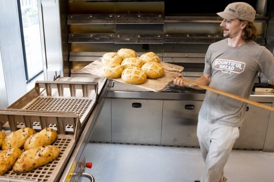 Justin Smith removes loaves of bread from the oven at Bountiful Bread on State Street; the bakery opened to the public Tuesday, June 22, 2021.
