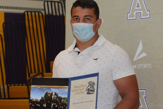 Amsterdam senior Alejandro Christopher displays his appointment to the United States Coast Guard Academy after a signing ceremony on June 1 at Amsterdam High School.