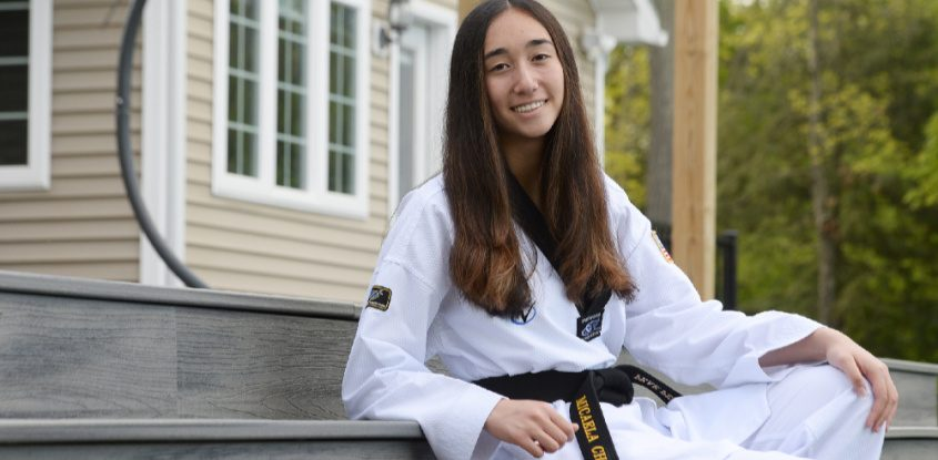 BH-BL senior Micaela Choi in her dobak, a takwondo uniform, surrounded by some of her best medals won, outside her home in Ballston Lake.