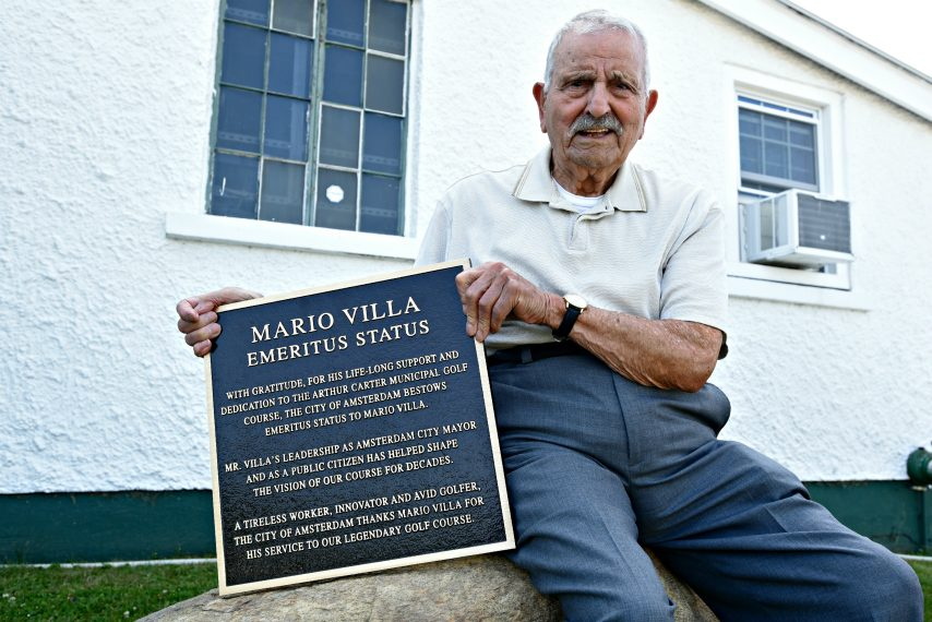 Former Amsterdam mayor Mario Villa sits on a boulder that will be adorned with a plaque, granting his emeritus status at Amsterdam Municipal Golf Course for his dedication to the course throughout his life.