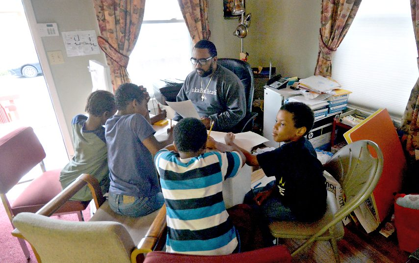 William Rivas works with kids after school at the COCOA House on Stanley St.