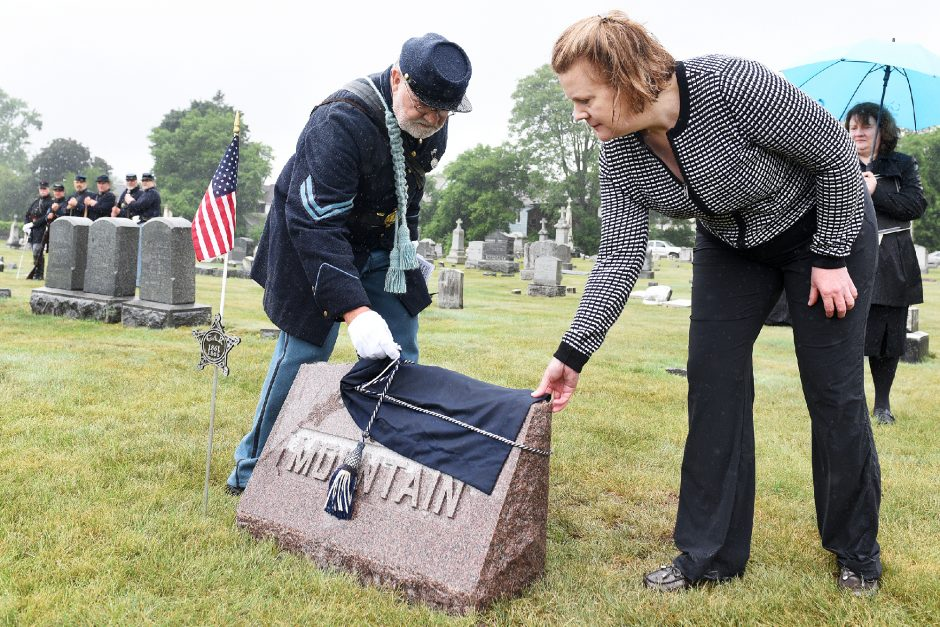 Julie Mountain and Civil War reenactor Rich Talay uncover a headstone for Civil War veteran Pvt. David Mountain, as Julie's sister Jennifer Mountain watches. A ceremony was held Friday to honor the Mountain sisters' great-great-grandfather at St. John the Baptist Cemetery in Schenectady.