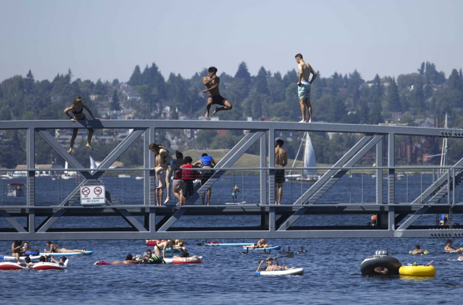 People jump from a pedestrian bridge at Lake Union Park into the water during a heat wave hitting the Pacific Northwest on Sunday, June 27, in Seattle. A day earlier, a record high was set for the day. (The Associated Press)