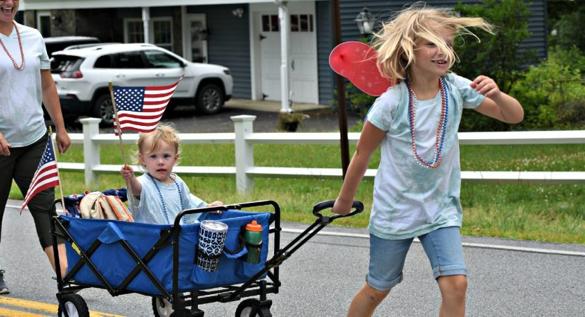 Emma James, 3, of Charlton, waves a flag as she is pulled by her cousin, Charlotte, 7, of Scotia during Sunday's annual 4th of July parade in the hamlet of Alplaus.
