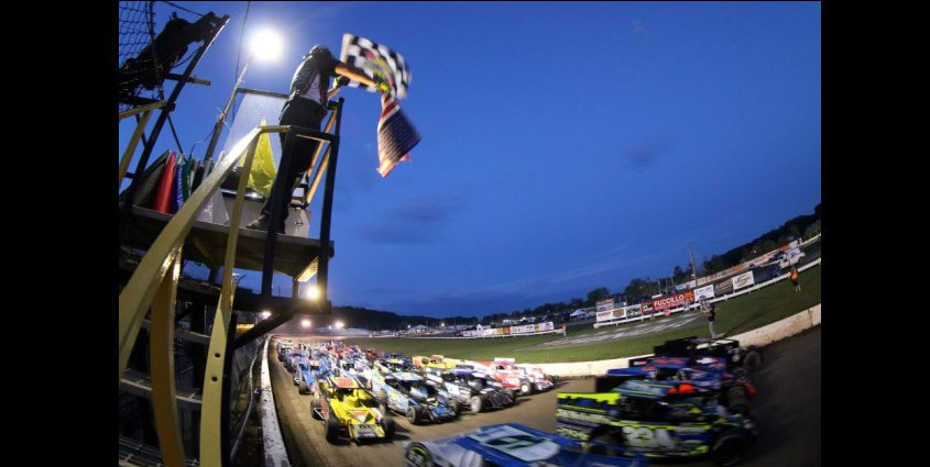 Flagger Joe Kriss salutes the four-wide modified formation to start the Firecracker 50 feature on Sunday at Fonda Speedway. (Photo courtesy Jeff Karabin)