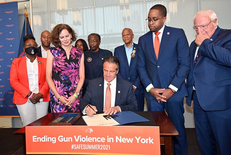 Gov. Andrew Cuomo signs a law opening the firearms industry to civil liability Tuesday. Looking on at left is Assemblymember Pat Fay, D-Albany, who led the effort to secure passage of the legislation in the Assembly.