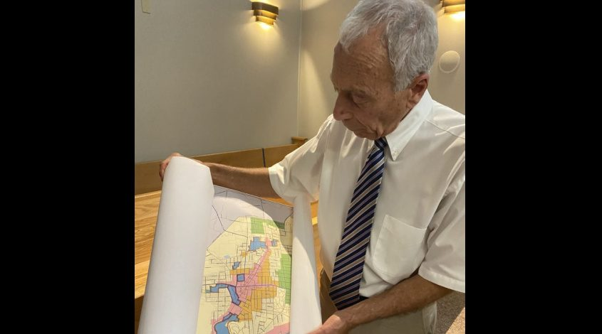 Mayor Vince DeSantis on Tuesday night at City Hall holds up a zoning map of the city of Gloversville that shows the 3-acre, square-shaped lot at 52 Church St.