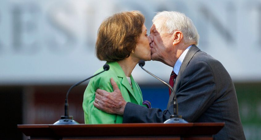 Former President Jimmy Carter gets a kiss from his wife Rosalynn as she introduces him during a reopening ceremony for the newly redesigned Carter Presidential Library in Atlanta in 2009