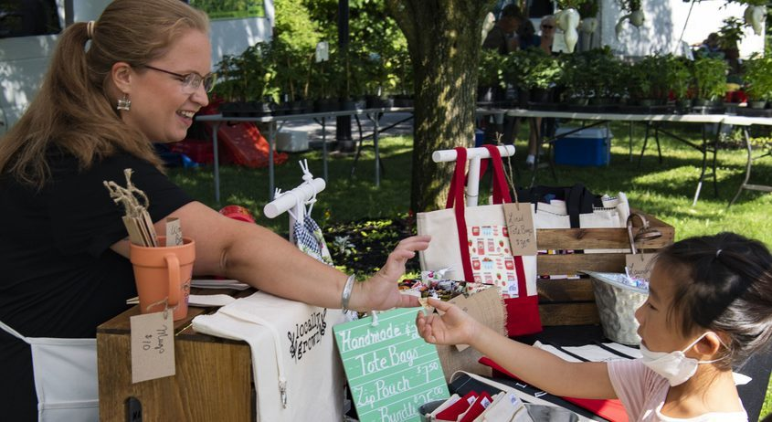 Erika Felpel owner of Erikraft Designs hands out stickers at her first Farmer's Market at Niskayuna Town Hall on Saturday.