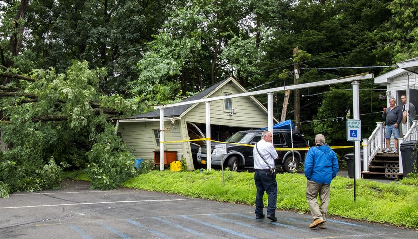 Scotia fire chief Kenneth Almy, left, and Glenville Codes Officer Arnold Briscoe talk to the owners of a home on North Ballston Avenue after a large tree branch came down on their garage Monday.