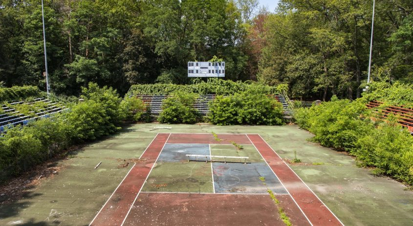 The once bustling World Team Tennis Stadium in Schenectady's Central Park is now overgrown and deserted, as seen on Thursday, July 15, 2021.