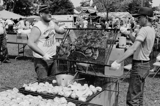 John Wood, left, and Charlie Dyer swing a rack of chicken over the fire during Mechanicville's Family Day on Sunday, July 6, 1986.