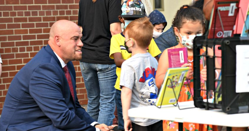 Incoming Schenectady superintendent of schools Anibal Soler, Jr. talks to an elementary school student as the Schenectady Reads bookmobile made its first stop of the summer at Howe Elementary School in Schenectady Tuesday morning.