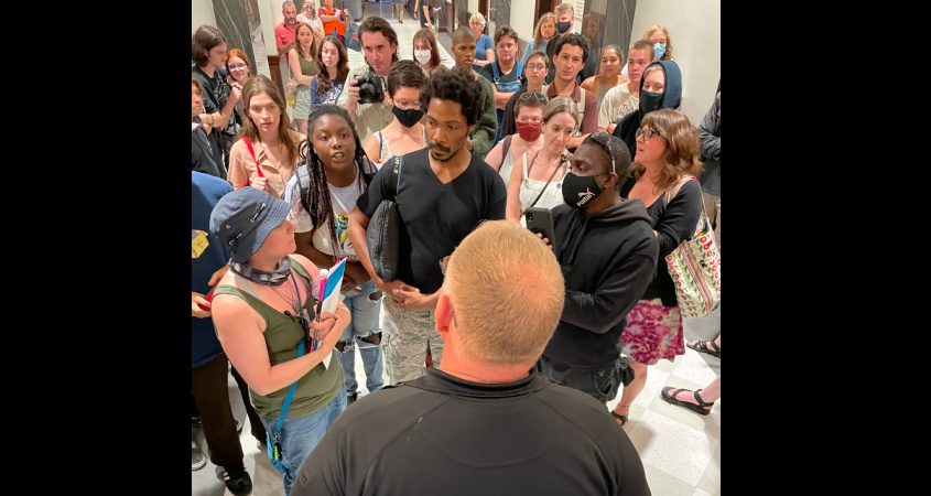 Protesters face off Tuesday evening with Saratoga Springs Police Lt. J. Mitchell in the hallway outside city council chambers.