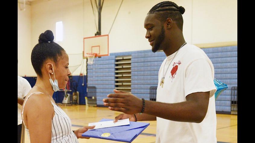 Recent Schenectady High School graduate Jeremiah Davis receives The Naylon Carrington #NayWay #Blueprint Project Foundation Athletic Scholarship Award from Sondra Banks Wednesday at Schenectady High School.