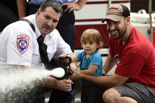 In this August 2018 photo, Colden Carucci, then 2, of Schenectady flows water with Schenectady firefighter Lt. Jeremy Matson, left, and his father Brian Carucci at Schenectady's National Night Out in Central Park that summer.