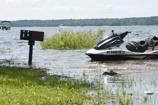 A public barbecue grill sits in several inches of water, near a jet ski on the shore of the Edinburg Town Park on Saturday, July 24, 2021, as recent heavy rainfall has caused the Great Sacandaga Lake to rise several feet in recent weeks.