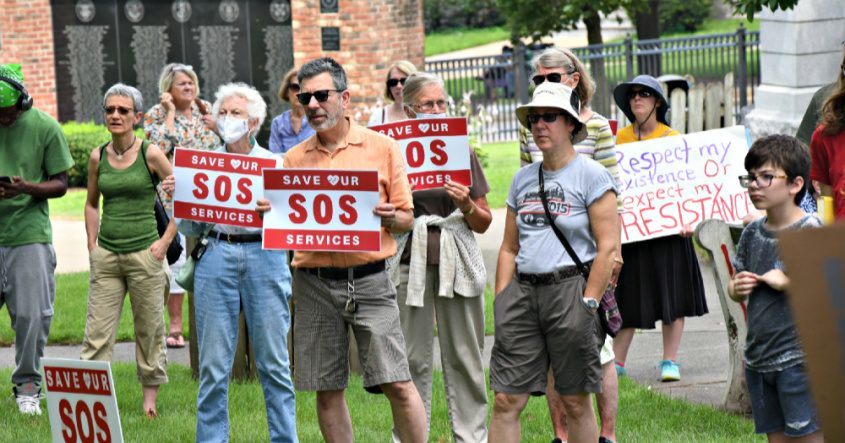 Attendees hold up signs during the Save our Services rally held by the Schenectady Coalition for Healthcare Access Sunday morning at Veteran's Park.