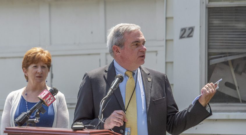Schenectady Mayor Gary McCarthy speaks beside Albany Mayor Kathy Sheehan during a press conference announcing lawsuits against Ocwen Financial Corporation and its subsidiary PHH Mortgage, while standing outside a zombie house at 22 1115th St. inTroy on Wednesday