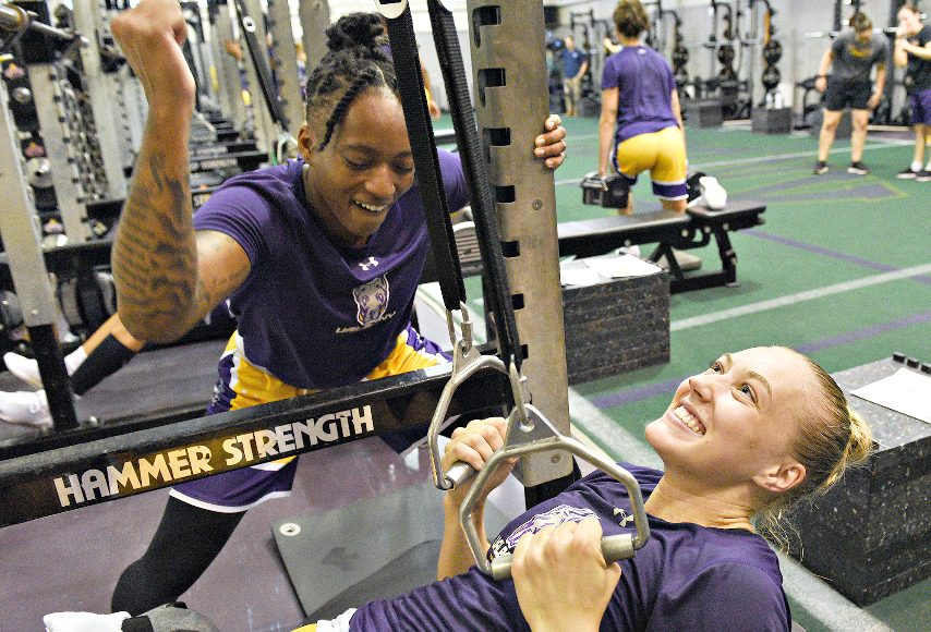 Fatima Lee, left, encourages teammate Ellen Hane during a weight-lifting session for the UAlbany women's basketball team.