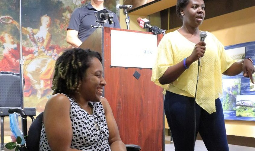 Liberty ARC client Imani Haynes listen to Theresa Wellington, a Liberty assistant manager, speak Thursday at an event to raise support for increased state funding for organizations that provide care for the disabled.