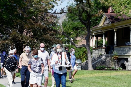 A Saratoga Springs Preservation Foundation Summer Stroll tour guide and her group walk down Union Ave during an August 2020 tour outside Saratoga Race Course in Saratoga Springs.