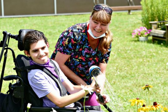 Jonah Weiss enjoys watering one of the flower beds with help from Sascha, a Niskayuna Support Staff employee on July 28 at the outdoor gardens on the Niskayuna High School campus.