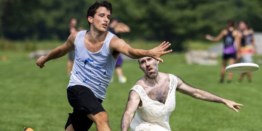 Jacob Adamson, left, tries to intercept a pass thrown by Grin, who is donning a wedding gown, during the Ow My Knee Ultimate Frisbee Tournament at Maalwyck Park in Glenville on Saturday, Aug. 7, 2021.