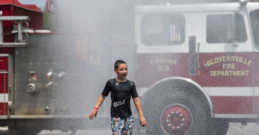 Seth Vannostrand, 8, cools off in the spray from a Gloversville fire truck at Railfest in Gloversville on Saturday, Aug. 7, 2021.