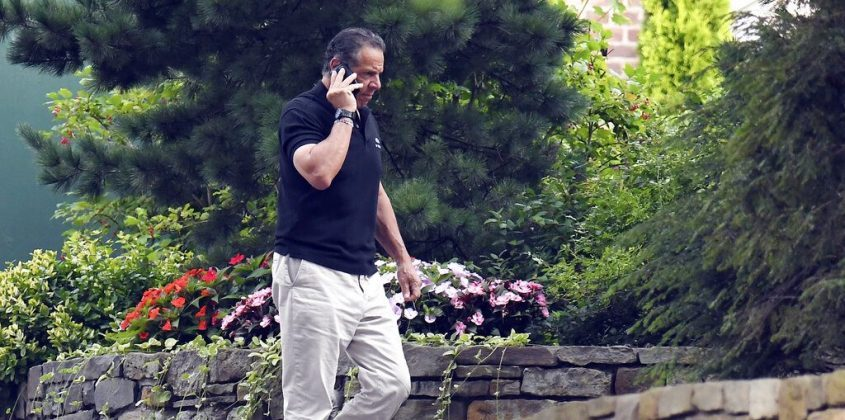 Gov. Andrew Cuomo talks on the phone while walking with his dog Captain at the New York state Executive Mansion, Saturday, Aug. 7, 2021, in Albany, N.Y. An investigation found that Cuomo sexually harassed multiple women in and out of state government.