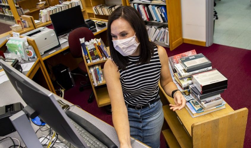 Rotterdam Library Clerk Jessica Cain scans returned books back into the computer system on Friday, August 13, 2021.