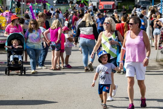 Sunshine Fair goers walk the midway in Cobleskill Saturday.