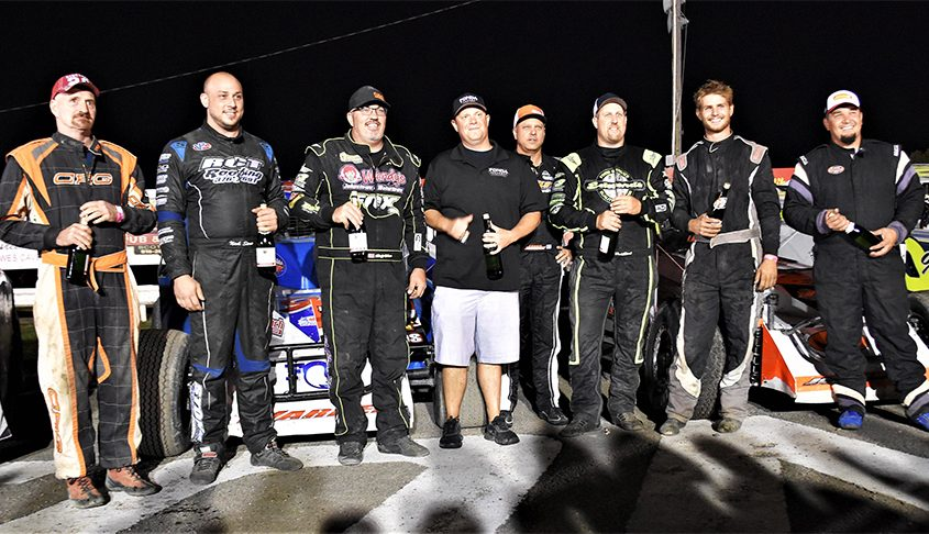 Fonda Speedway crowned its 2021 track champions Saturday night. From left: Ken Hollenbeck (4-cyl. SOHC), Nick Stone (pro stock), Rocky Warner (modified co-champion), Fonda Speedway promoter Brett Deyo, Ronnie Johnson (modified co-champion), Chad Edwards (602 sportsman), Carter Gibbons (limited sportsman) and Slappy White (4-cyl, DOHC). (James A. Ellis photo)