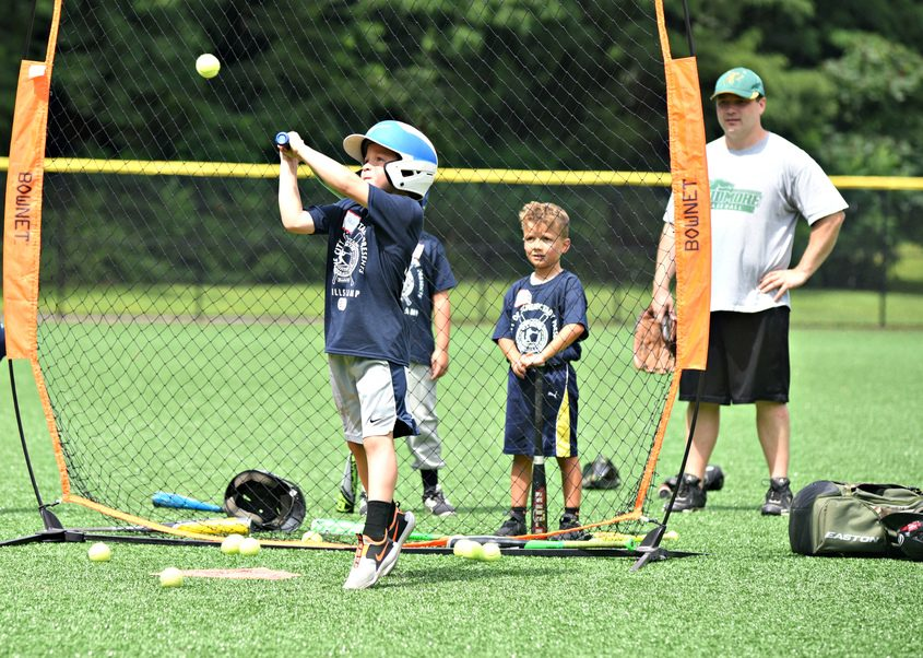 A young camper reaches up on his swing during the first day of a two-day camp at the Central Park A Diamond in Schenectady, sponsored by the Schenectady Old Timers Baseball Club ug. 16, 2021.